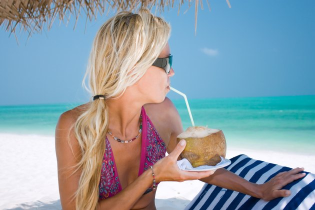 Beautiful blondy holding coconut