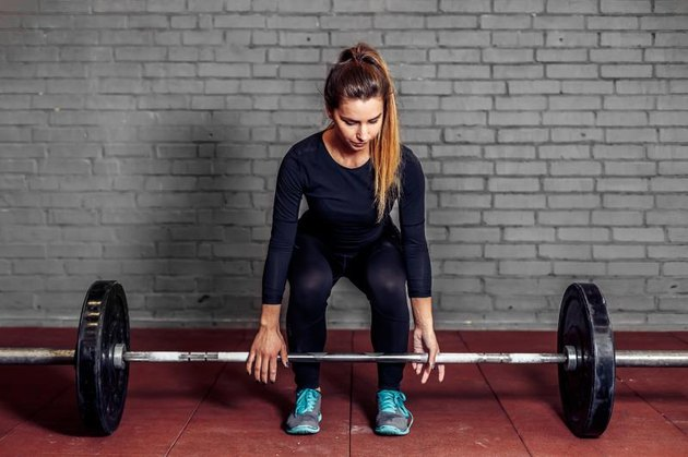 Female athlete doing deadlift at the gym with weight bar. Fitness girl in great shape is lifting weights in a sport gym. Athletic woman train workout.
