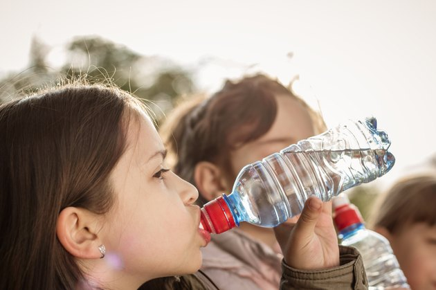 Photo of little girls drinking water with a friends