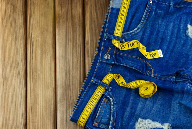 Jeans with measuring tape on wooden background