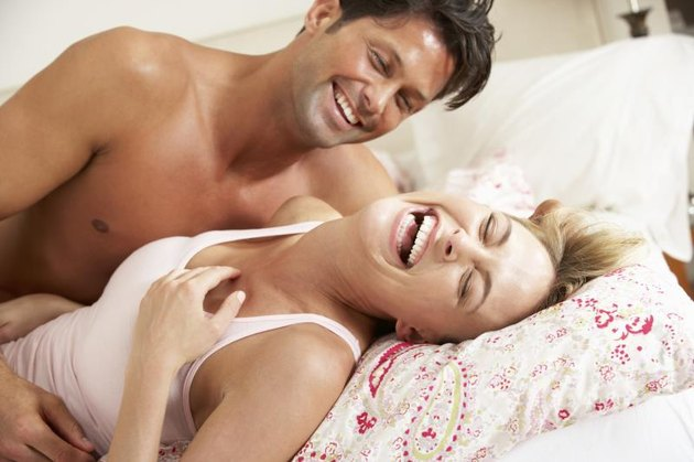 Couple Relaxing Together In Bed Lying Down Laughing