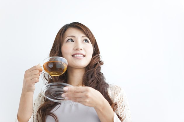Young woman holding cup of tea, copy space