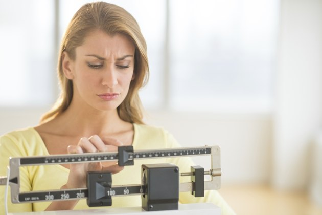 Woman Using Balance Weight Scale At Gym