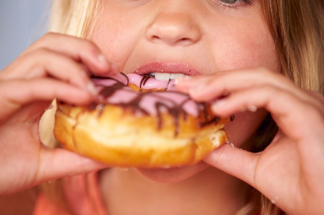 Close Up Of Girl Eating Iced Donut