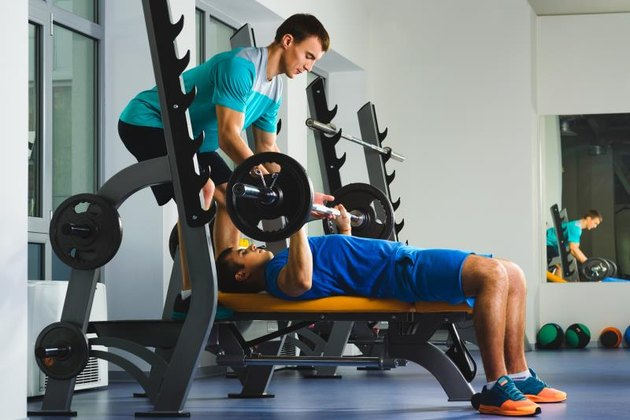 Young Man In Gym Exercising Chest On The Bench Press with bar.