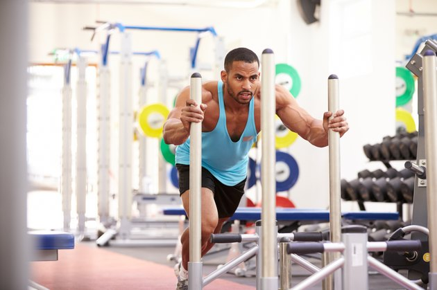 Muscular man working out using equipment at a gym