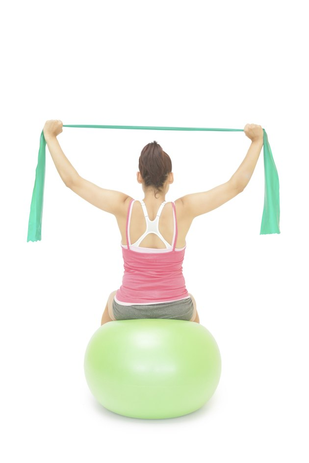Sporty brunette stretching with resistance band sitting on exercise ball