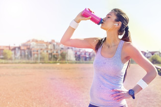 Young sportswoman drinking water after running