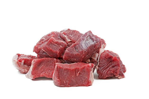 Pieces of raw beef goulash, isolated on white