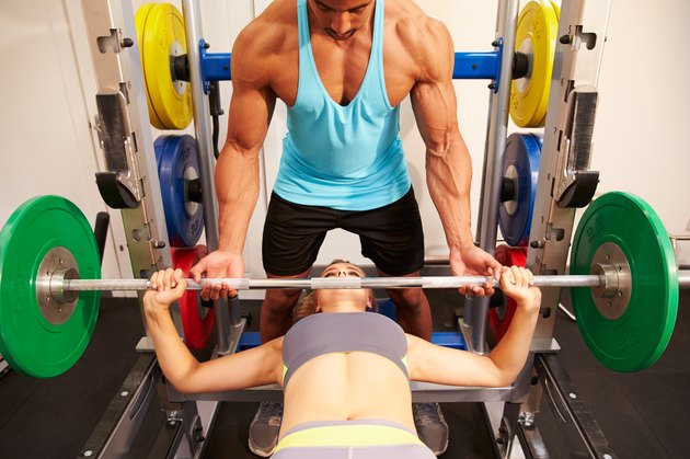 Woman bench pressing weights with assistance of trainer, front v