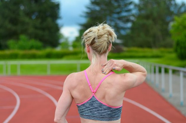 Rear view of athletic female sprinter massaging her own neck at race track with trees in background