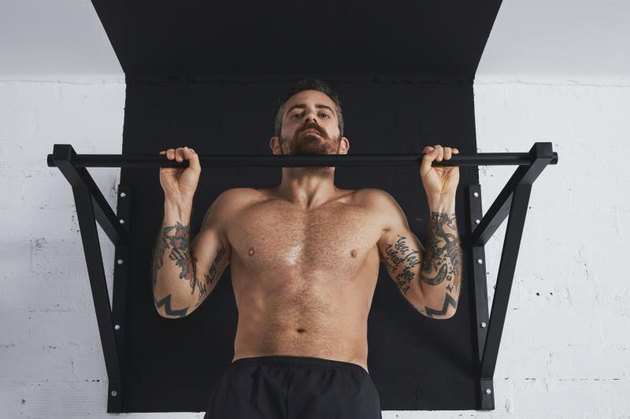 Tattooed male athlete performs a pullup variation called an inverted row.
