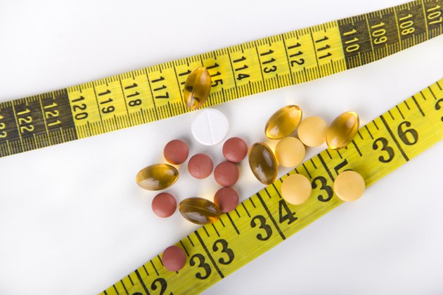 Diet Pills with yellow measuring tape
