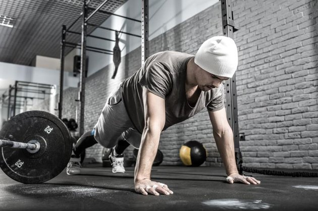 Nice guy with a beard prepares to make a pushup in the gym on the gray brick wall background. He wears sportswear, white sneakers and a white cap. Man looks at the floor. Horizontal.