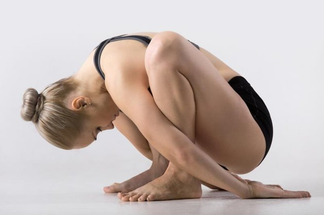 Sporty beautiful young woman practicing yoga, sitting in squat, variation of Garland Pose, Malasana with forward bend, working out wearing black sportswear, studio