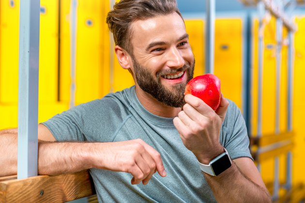 Man with apple in the gym
