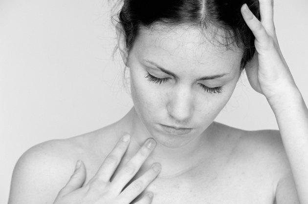 Young woman with bare shoulders in deep reflective thought.