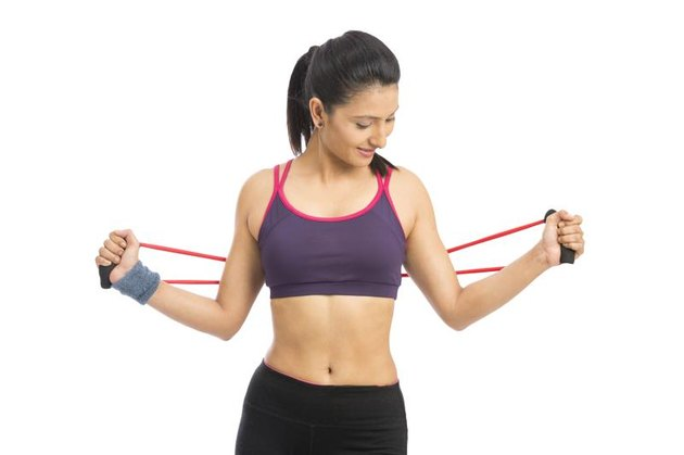 young fit women working out with rubber band over white background