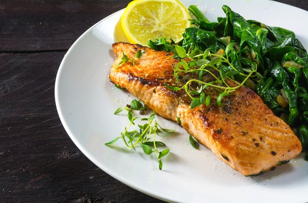 grilled salmon withspinach on a white plate, dark wooden table