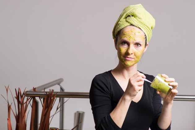 Attractive young woman with spots using a facial avocado mask