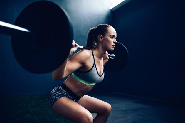 Young female athlete doing squat with barbell in gym gym