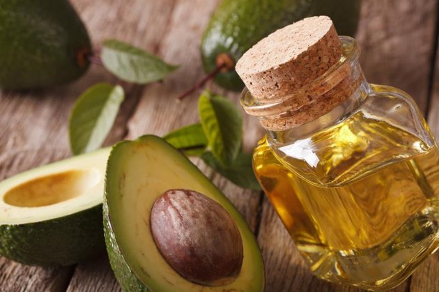 avocado oil in a glass bottle on a table close-up. Horizontal