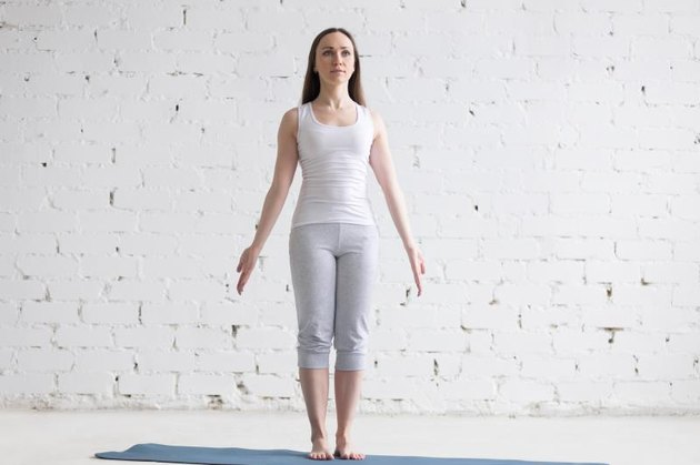 Attractive happy young woman working out indoors. Front view portrait of beautiful model doing yoga exercise on blue mat. Standing in Tadasana, Mountain Pose. Full length