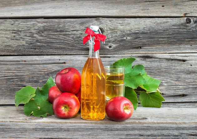 composition with apple juice in the bottle and apples