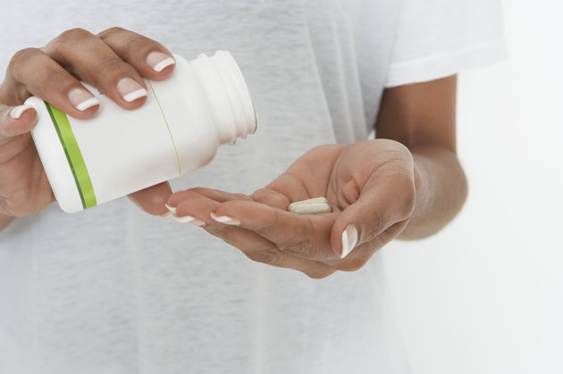Woman holding bottle of pills, mid section