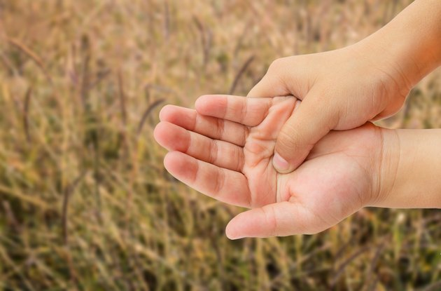 Close up hand pain with grass blurred background