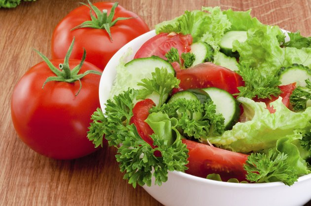Bowl of mixed salad against and tomatoes is wooden table
