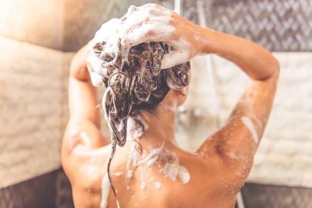 Back view of beautiful naked young woman is using shampoo while taking shower in bathroom