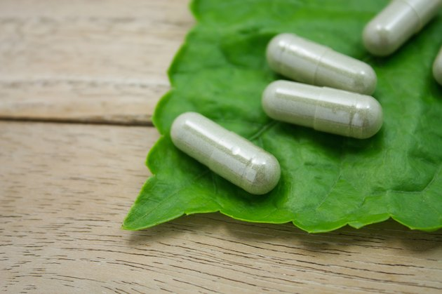 herbal medicine capsules with green herb leaf on wood table