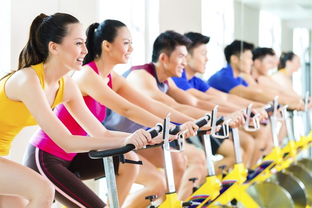 Asian people spinning bike training at fitness gym