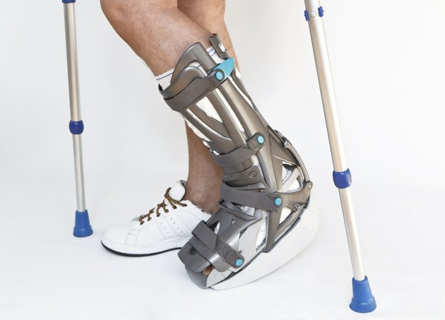 Man with a broken leg walking on crutches