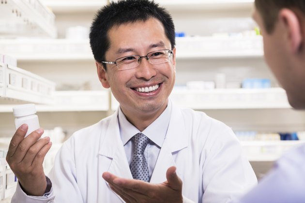 Smiling pharmacist showing prescription medication to a customer