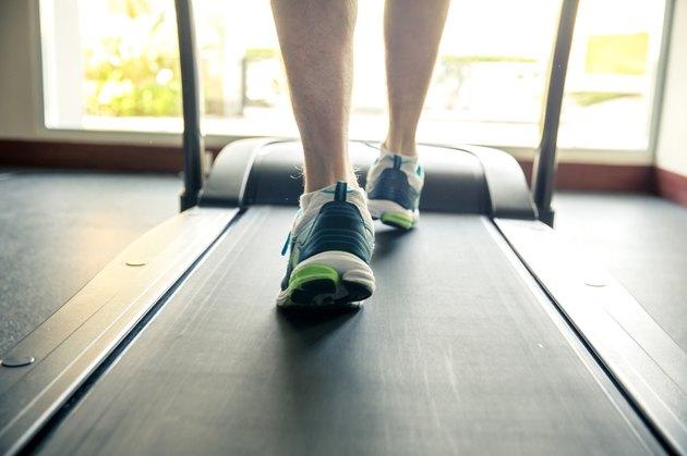 Young men walking on treadmill