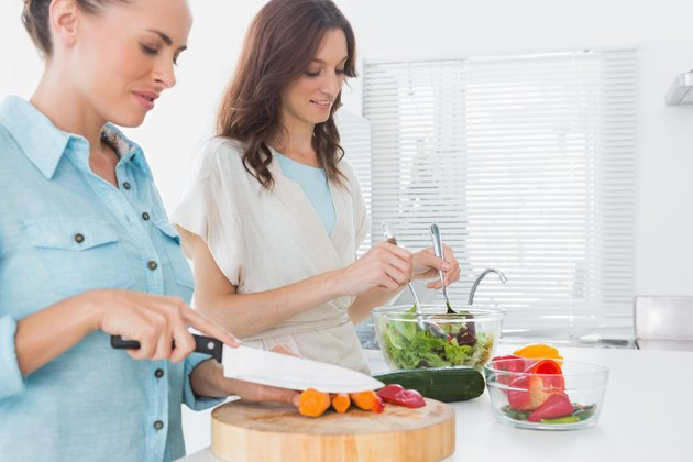 Women preparing salad together