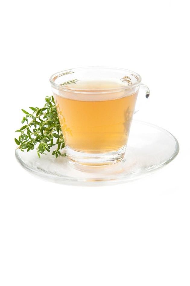 thyme tea with fresh herbs beside teacup,