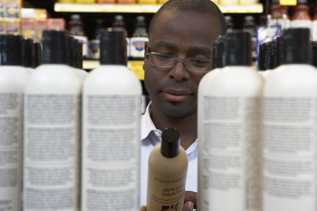 Man reading shampoo label in store, close-up