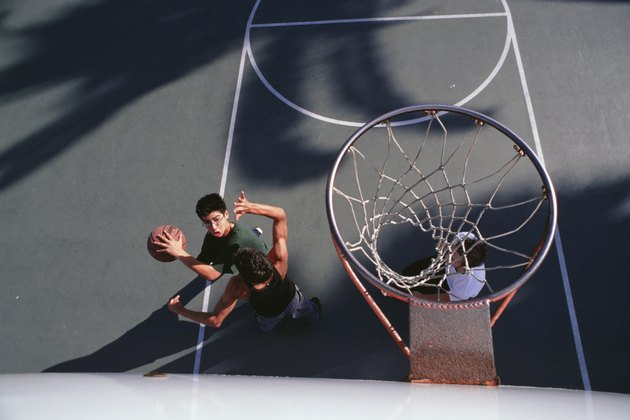 Three teenage boys (16-17) playing basketball, elevated view