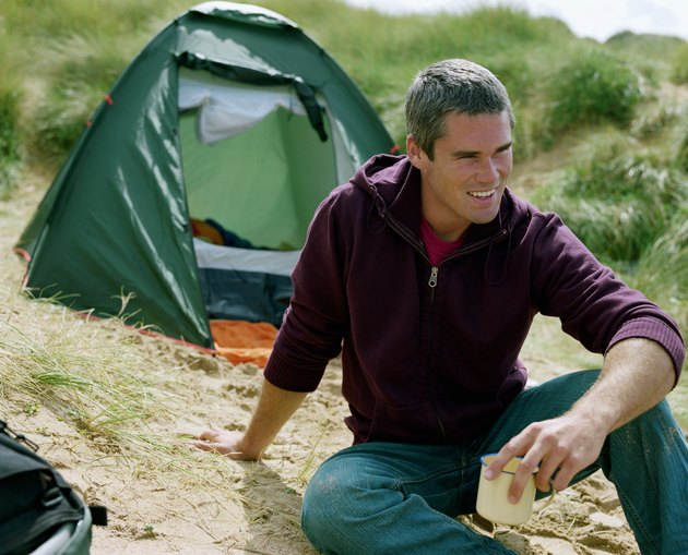 Young man sitting on sand by tent, holding cup, looking away, smiling