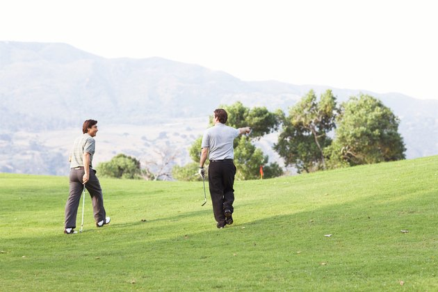 Golfers walking on green