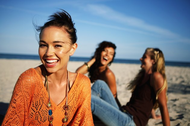Young women smiling on beach, portrait, close-up (focus on foreground)