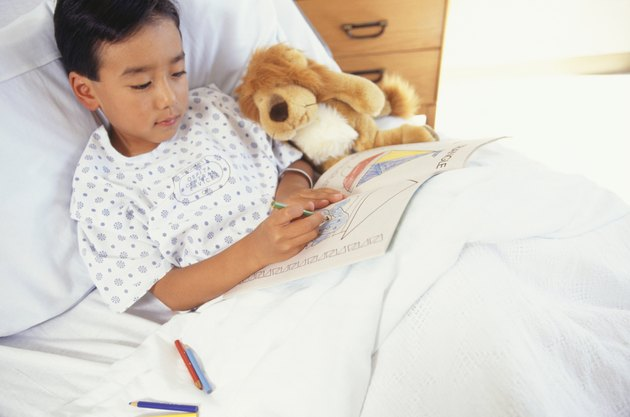 Boy (6-7) lying in hospital bed with toy animal, drawing in book