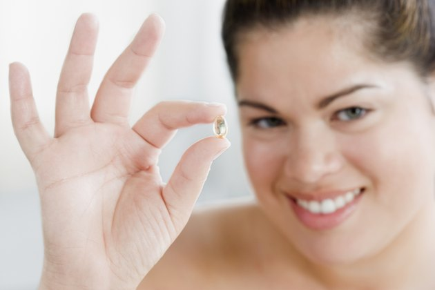 Close up of Hispanic woman holding vitamin