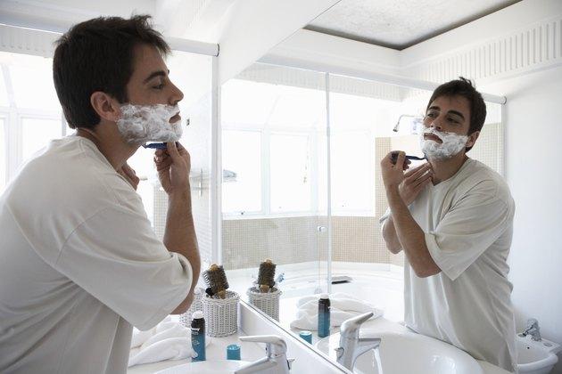 Man shaving face in bathroom mirror, side view