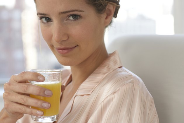 Young woman wearing pyjamas holding glass of juice, close-up, portrait