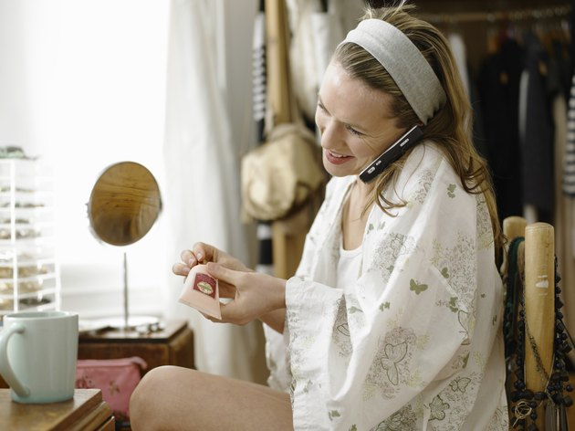 Young woman sitting at dressing table using cell phone, smiling