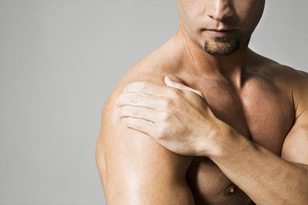 Man massaging shoulder, mid section